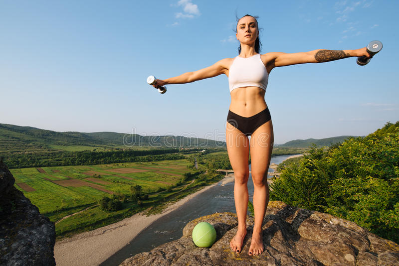 fit brunette woman doing exercises with dumbbells outdoor. Training in the mountain peak. Green mountains royalty free stock images