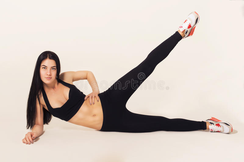 fit brunette woman in sportswear lying on the floor, do exe royalty free stock images