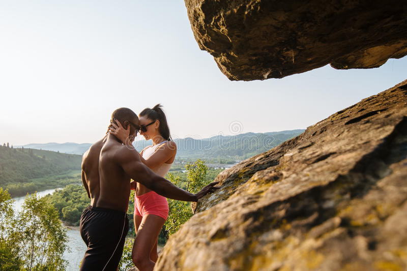 Fit mixed race couple with perfect bodies in sportswear posing on the rocky mountains landscape. Full-length fashion portrait, sport and lifestyle concept stock image