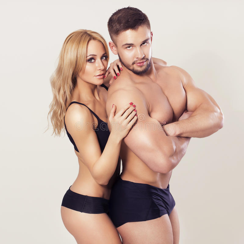 fit muscled couple in sportswear on neutral grey background stock image