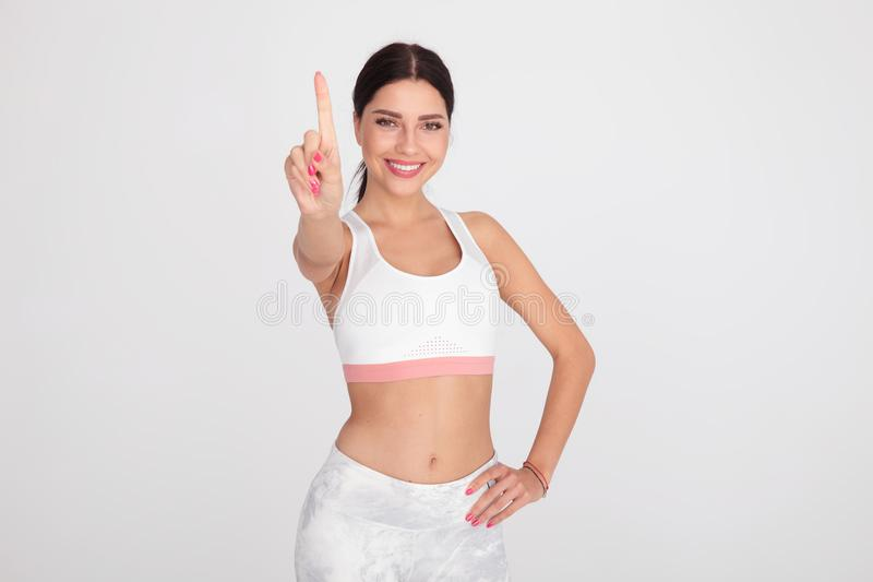 Fit woman in white gym outfit pointing finger up. Portrait of fit woman in white gym outfit pointing finger up while standing on light grey background stock photography