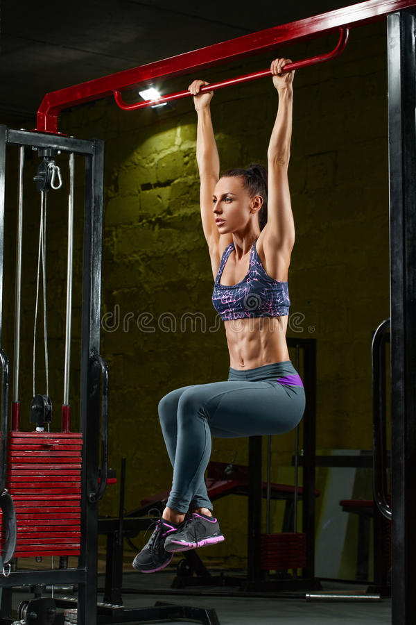 Fitness girl doing pulls up on horizontal bar in gym. Muscular woman, abs, shaped abdominal.  royalty free stock photography