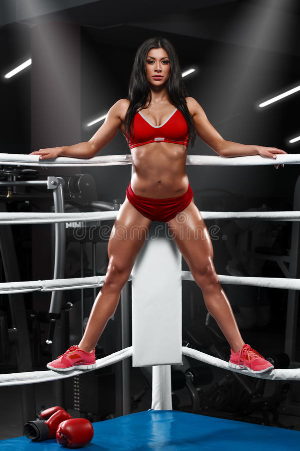 fitness girl showing muscular athletic body, abs. Muscular woman in the boxing ring stock photos