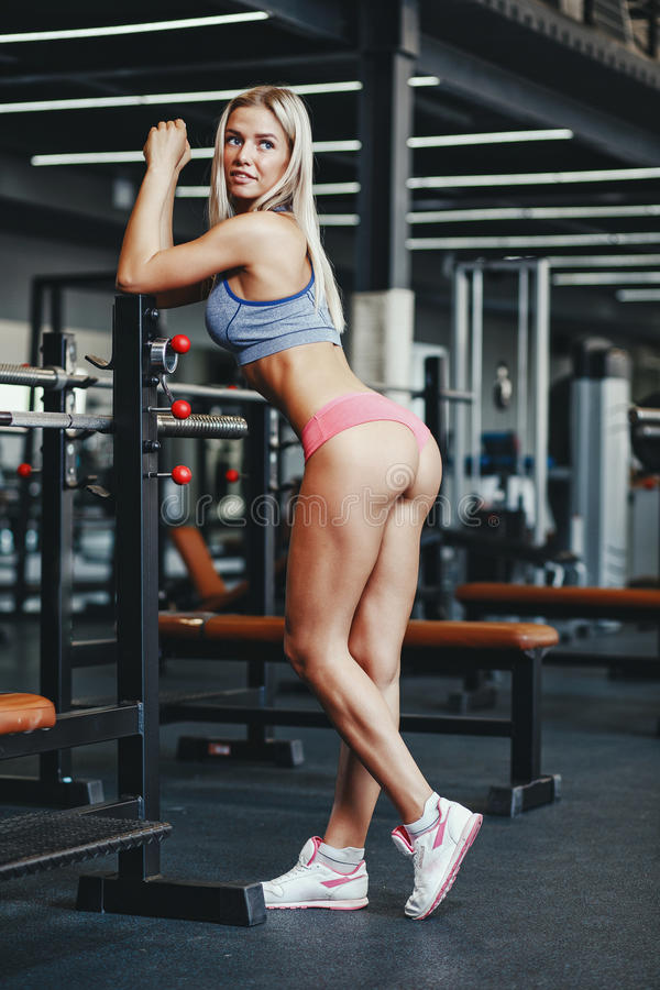 Fitness happy blonde girl in sport wear with perfect body in the gym posing and smiling. Fitness happy blonde girl in sport wear with perfect body in the gym stock photo