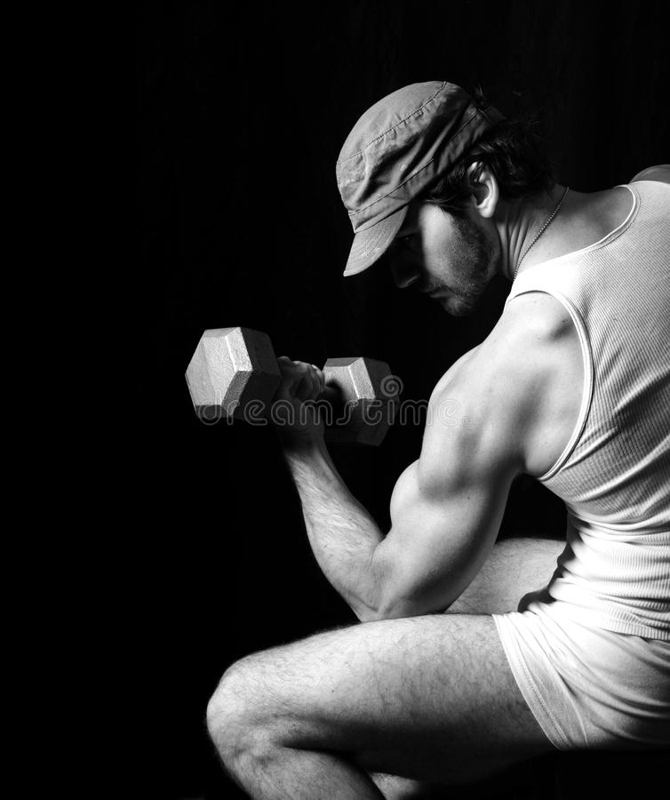 Fitness model. Black and white fitness fashion portrait of very muscular fit male model doing bicep curl against black background royalty free stock images