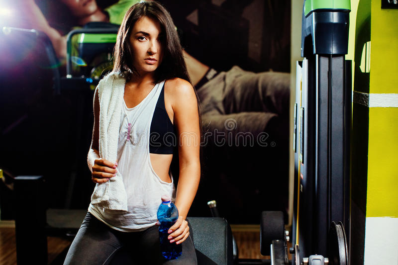Fitness woman drink water in gym. Long hair sporty woman royalty free stock photography