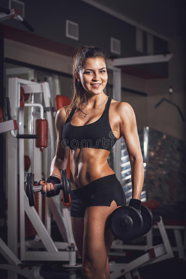 fitness woman with a dumbbell in the gym royalty free stock photography
