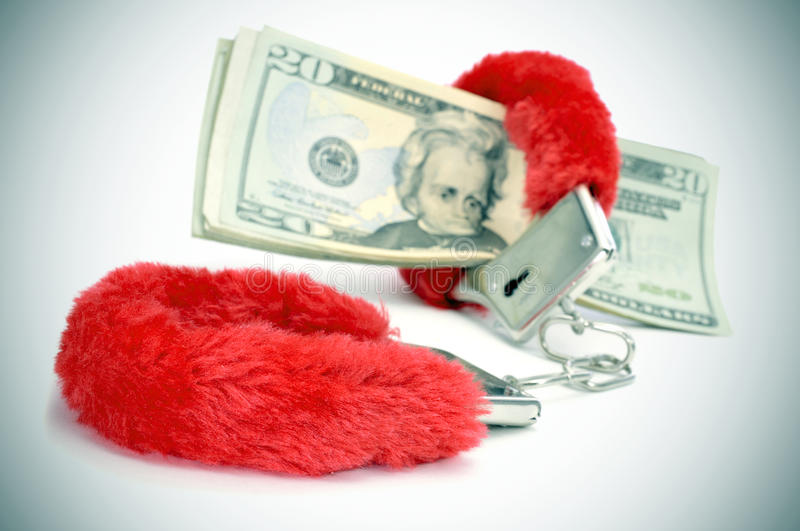Fluffy handcuffs and dollar bills. A pair of red fluffy handcuffs and some dollar bills depicting the idea of paying for sex or the sex industry or the sex royalty free stock photos