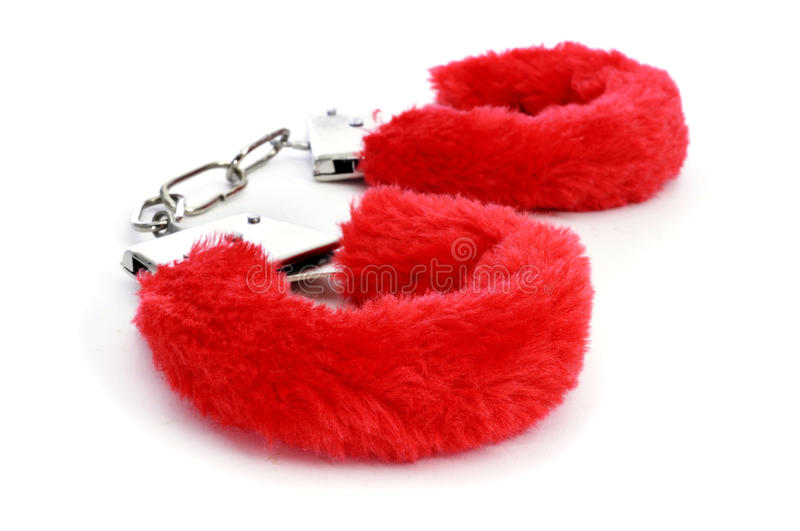 Fluffy handcuffs. A pair of red fluffy handcuffs on a white background royalty free stock photos