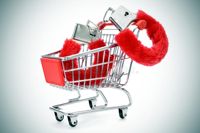 Fluffy handcuffs in a shopping kart. A pair of red fluffy handcuffs in a shopping cart depicting the idea of paying for sex or the sex industry or the sex royalty free stock images
