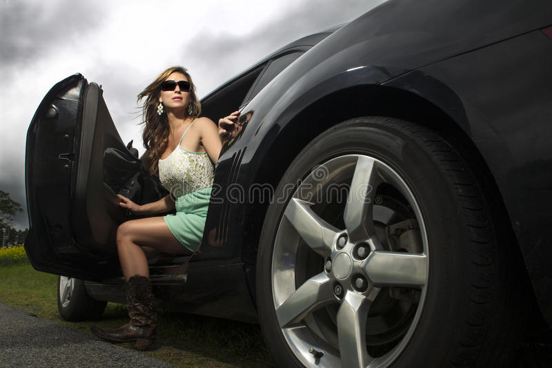 Sexy Frau beim Stiefelverlassen ein Auto lizenzfreies stockfoto