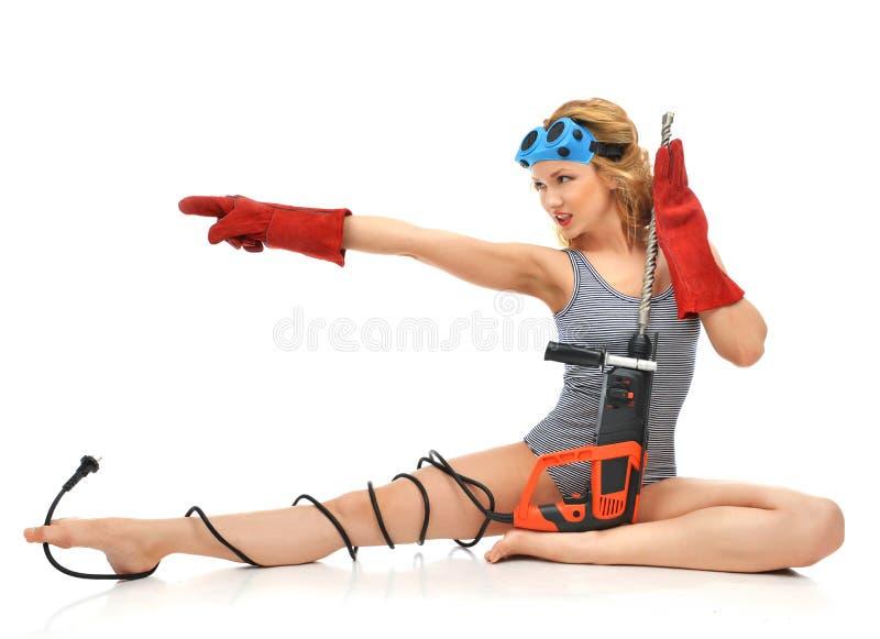 Sexy Frau contructor Arbeitskraft, die mit Baubohrgerätesprit sitzt lizenzfreie stockbilder