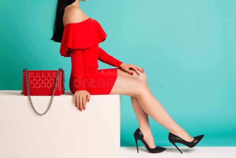 Sexy Frau in den hohen Absätzen mit roter Tasche auf einem blauen Hintergrund stockbilder