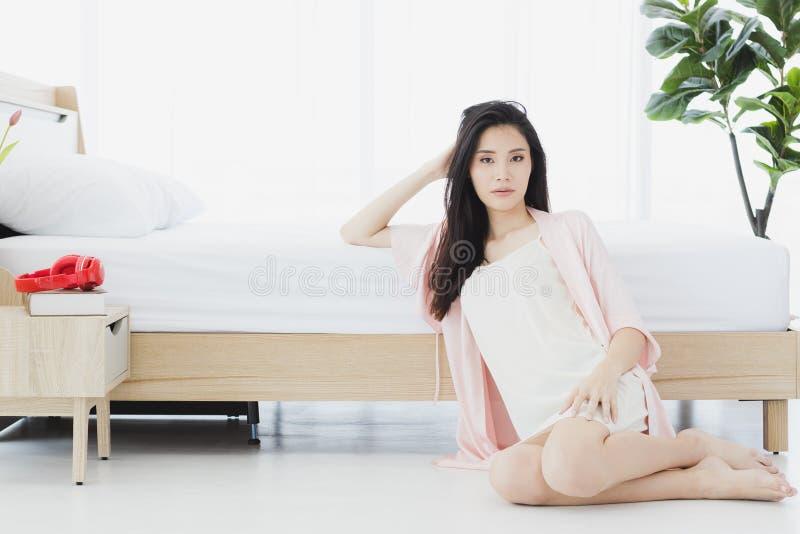 Sexy Frau in den Pyjamas, die auf Boden im Schlafzimmer sitzen lizenzfreie stockbilder