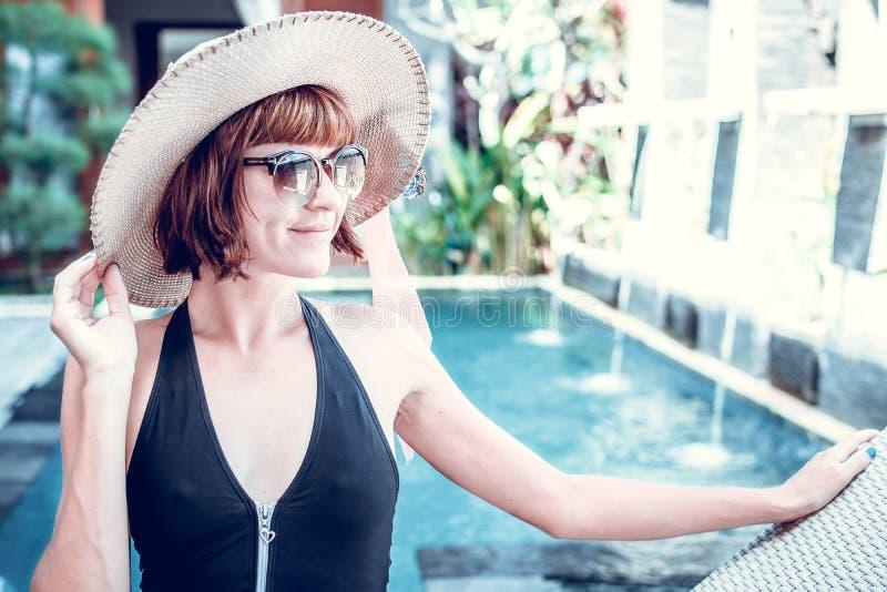 Sexy Frau der Schönheit mit Hut und Sonnenbrille ihre Sommerferien am Swimmingpool auf einem Luxuslandhaus genießend Sommer stockbild