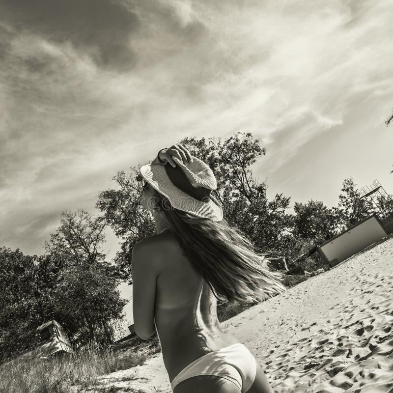 Sexy Frau des Bikinis in der Sonnenbrille und in einem Hut lizenzfreies stockbild