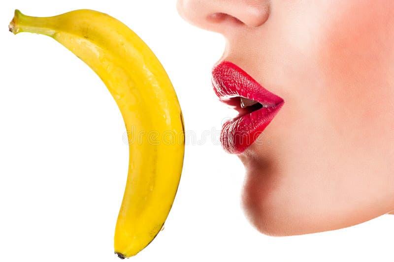 Sexy Frau, die Banane, sinnliche rote Lippen isst lizenzfreie stockbilder