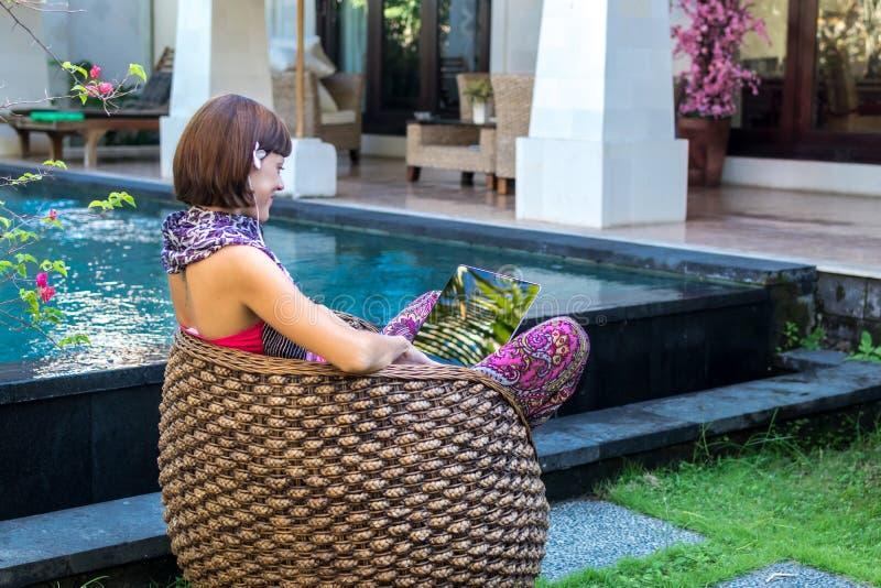 Sexy Frau, die draußen Laptop-Computer auf einem Aufenthaltsraum nahe Swimmingpool verwendet Tropischer Garten von Bali-Insel, In stockfotografie