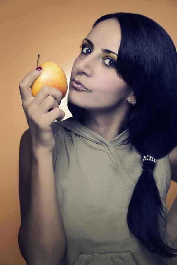 Sexy Frau, die einen Apfel küsst stockfotografie