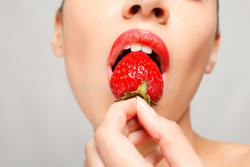 Sexy Frau, die Erdbeere isst Sinnliche rote Lippen stockbilder