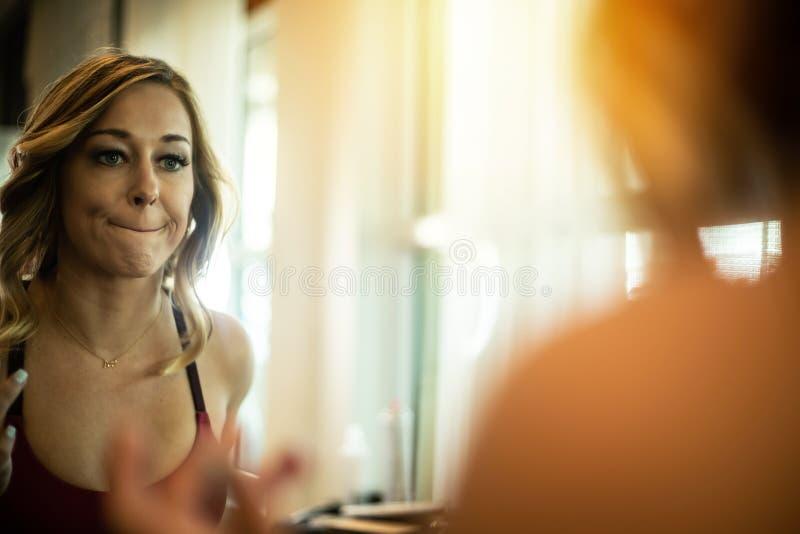 Sexy Frau, die Lippenstift im Spiegel anwendet stockfotografie