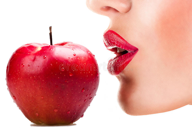 Sexy Frau, die roten Apfel, sinnliche rote Lippen isst stockfoto