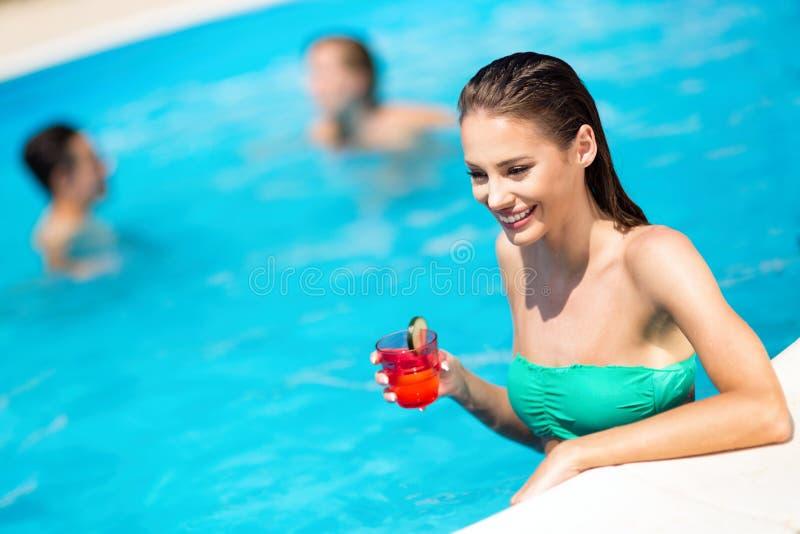 Sexy Frau, die Sommer im Pool und im Lächeln genießt stockfotografie