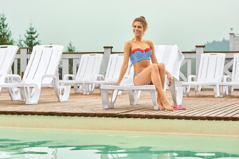 Sexy Frau, die Sommerferien nahe Pool am Erholungsort genießt lizenzfreie stockfotos