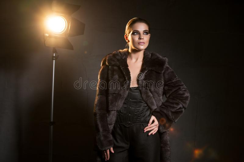 Sexy Frau in einem modernen Tannenmantel in der Dunkelheit lizenzfreie stockbilder