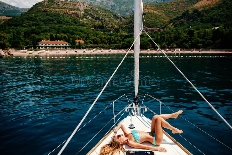 Sexy Frau entspannen sich auf Yacht im Meer lizenzfreie stockbilder