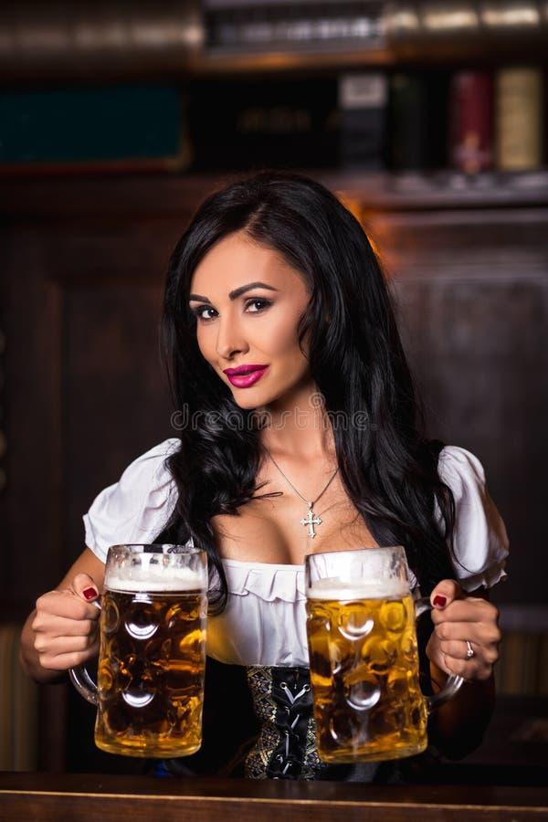 Sexy Frau im Dirndlkleid, das Oktoberfest-Bierbierkrug hält lizenzfreie stockfotos