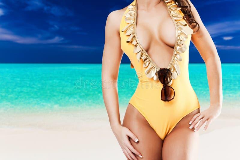 Sexy Frau im gelben Bikini vor tropischem Strand mit Blau stockfotos