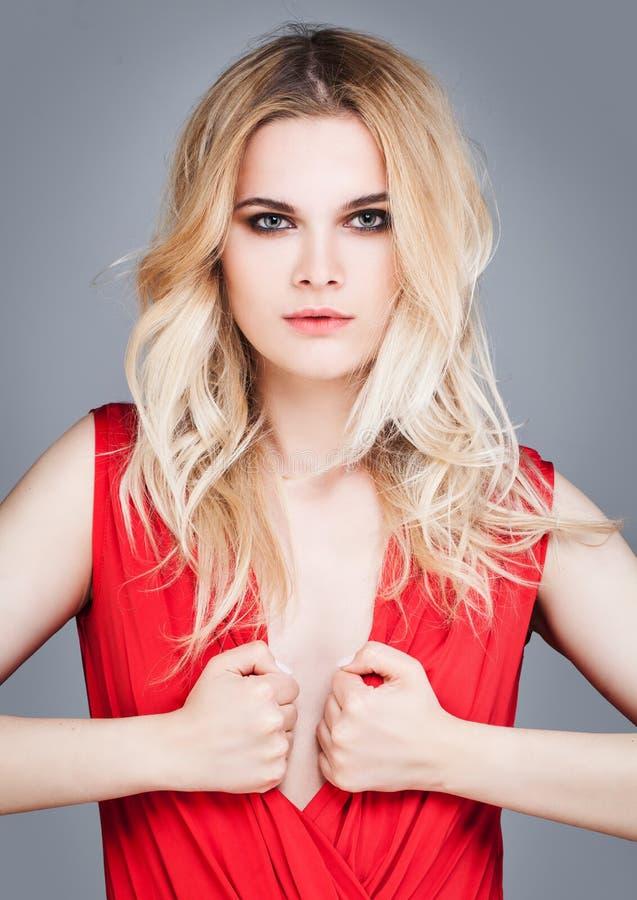 Sexy Frau mit blondes Haar-tragendem Rot lizenzfreies stockbild