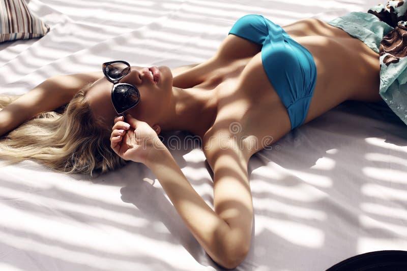 Sexy Frau mit dem blonden Haar im Bikini und in Sonnenbrille, die auf Strand sich entspannen stockfotografie