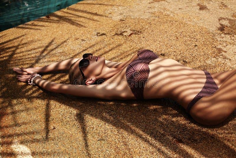 Sexy Frau mit dem blonden Haar im eleganten Bikini, der auf Strand sich entspannt stockbilder