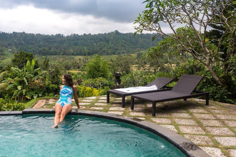 Sexy Frau, welche die Sonne am Unendlichkeitssommer-Swimmingpool am luxuriösen Erholungsort genießt lizenzfreie stockbilder