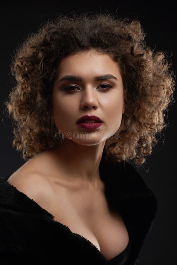 Sexy gelockte Frau, die im Studio aufwirft stockfotos