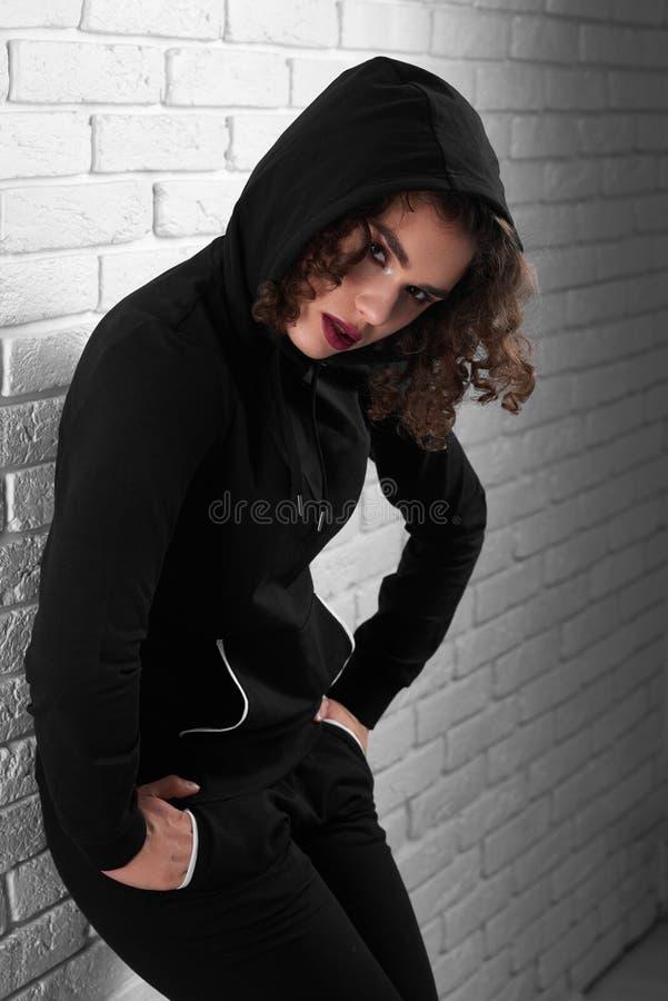 Sexy gelocktes exotisches girlin die Haube, die nahe weißer Wand aufwirft stockfoto