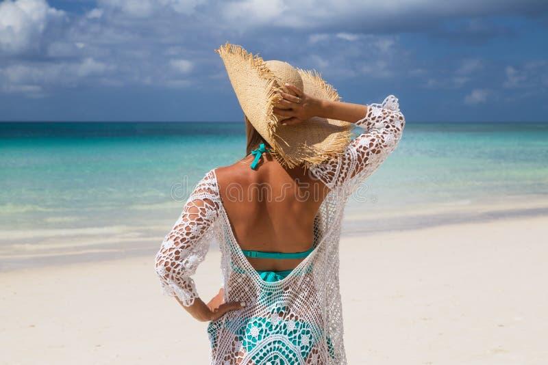 Sexy gelooid meisje in blauwe bikini, strohoed die van zich erachter op de kust bevinden Het mooie model zonnebaadt en rust op ov royalty-vrije stock afbeeldingen