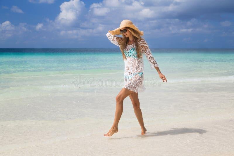 Sexy gelooid meisje die in blauwe bikini en witte tunica op de kust lopen Het mooie model zonnebaadt en rust op overzees Concept stock foto