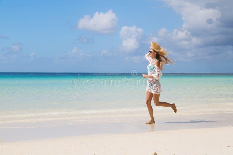 Sexy gelooid meisje die in blauwe bikini en witte tunica op de kust lopen Het mooie model zonnebaadt en rust op overzees Concept stock afbeelding