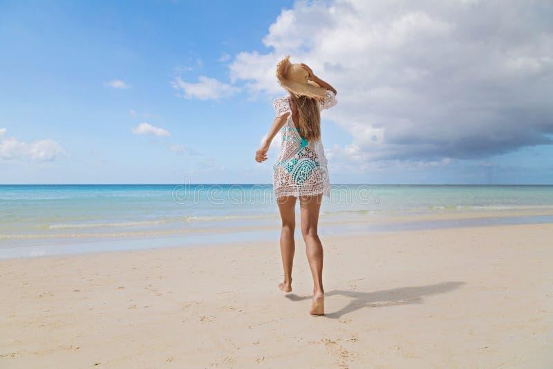 Sexy gelooid meisje die in blauwe bikini en witte tunica op de kust lopen Het mooie model zonnebaadt en rust op overzees Concept royalty-vrije stock fotografie