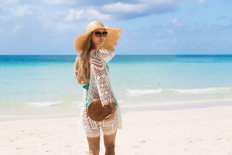 Sexy gelooid meisje die in blauwe bikini en witte tunica zich op de kust bevinden Het mooie model zonnebaadt en rust op overzees  stock foto