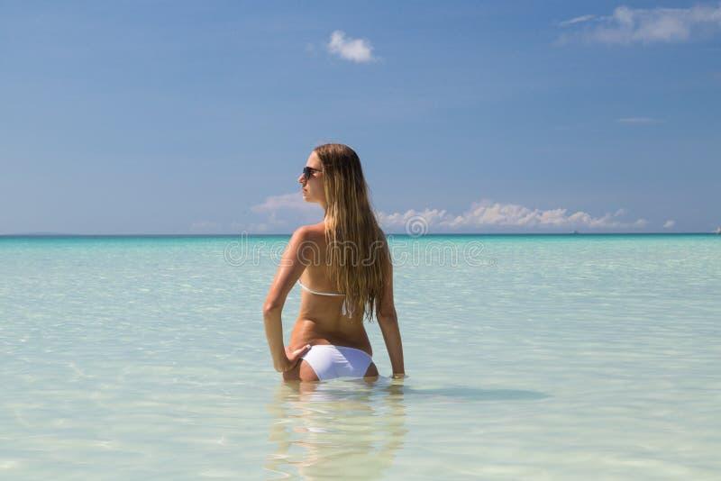 Sexy gelooid meisje in het witte zwempak stellen op het overzees Het mooie model zonnebaadt en rust op oceaankust Conceptenvakant stock afbeelding
