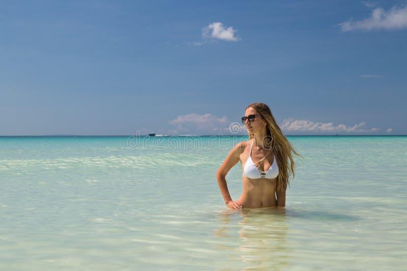 Sexy gelooid meisje in het witte zwempak stellen op het overzees Het mooie model zonnebaadt en rust op oceaankust Conceptenvakant stock foto