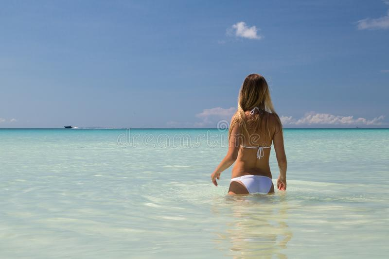 Sexy gelooid meisje in het witte zwempak stellen op het overzees Het mooie model zonnebaadt en rust op oceaankust Conceptenvakant stock fotografie