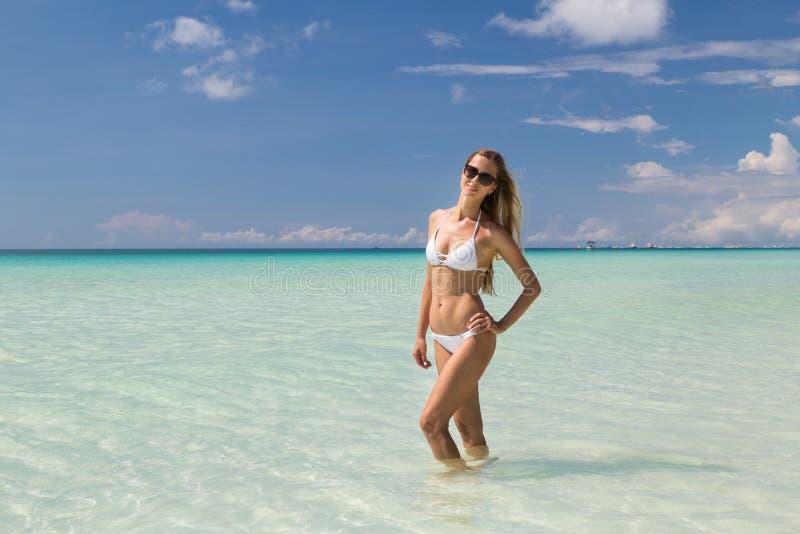 Sexy gelooid meisje in het witte zwempak stellen op het overzees Het mooie model zonnebaadt en rust op oceaankust Conceptenvakant royalty-vrije stock afbeelding