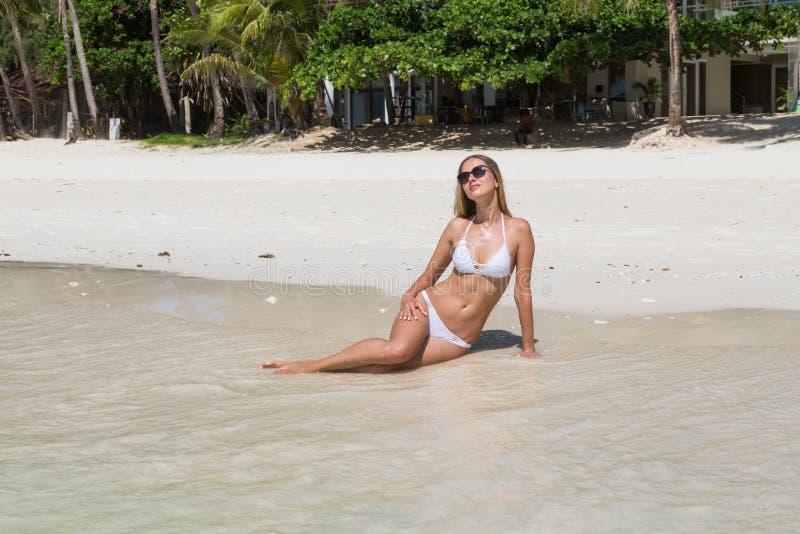Sexy gelooid meisje in het witte zwempak stellen op zandig strand Het mooie model zonnebaadt en rust op oceaankust Conceptenvakan royalty-vrije stock fotografie