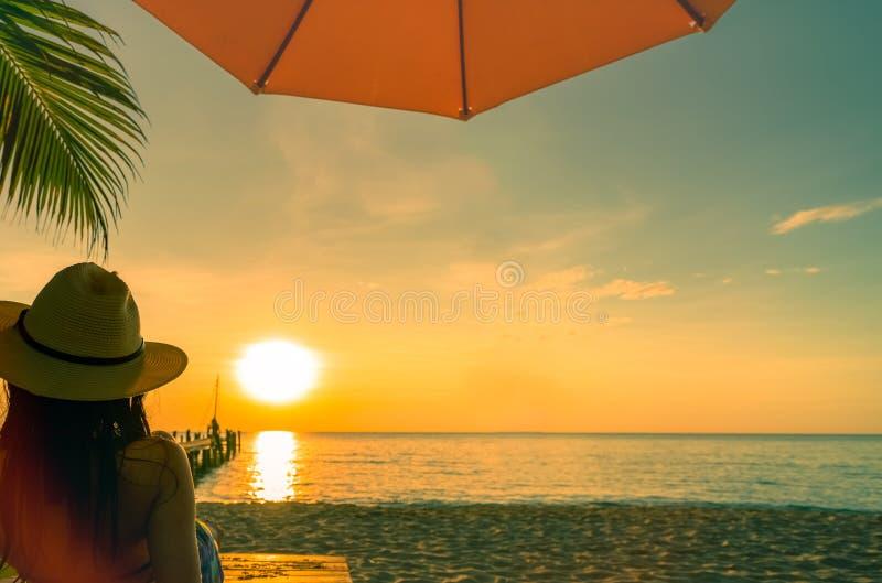 Sexy, geniet en ontspan van de bikini van de vrouwenslijtage liggend en het zonnebaden sunbed bij zandstrand bij paradijs tropisc stock foto's