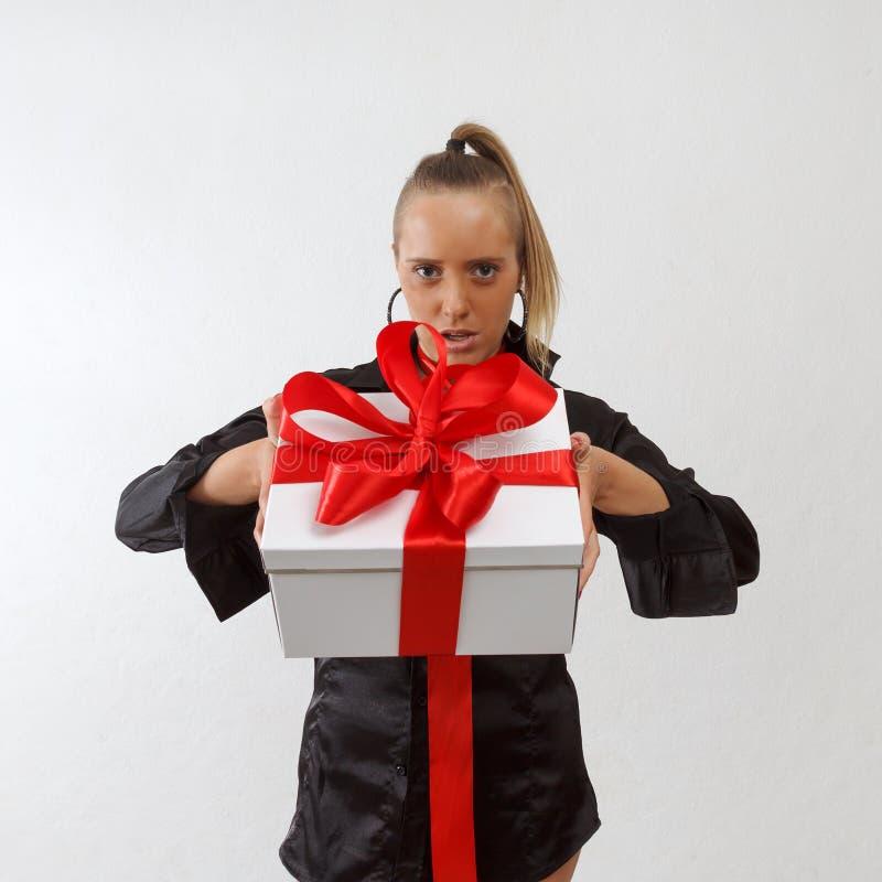 Sexy Geschäftsdame, die Geschenkbox mit rotem Band hält stockbild